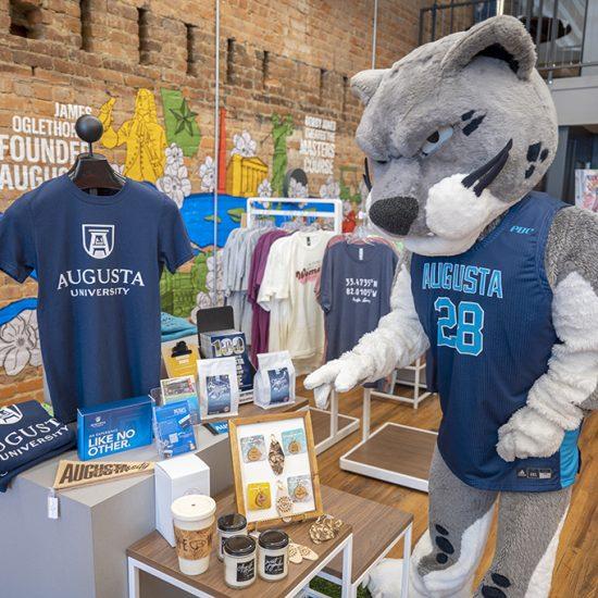 Mascot in front of merchandise