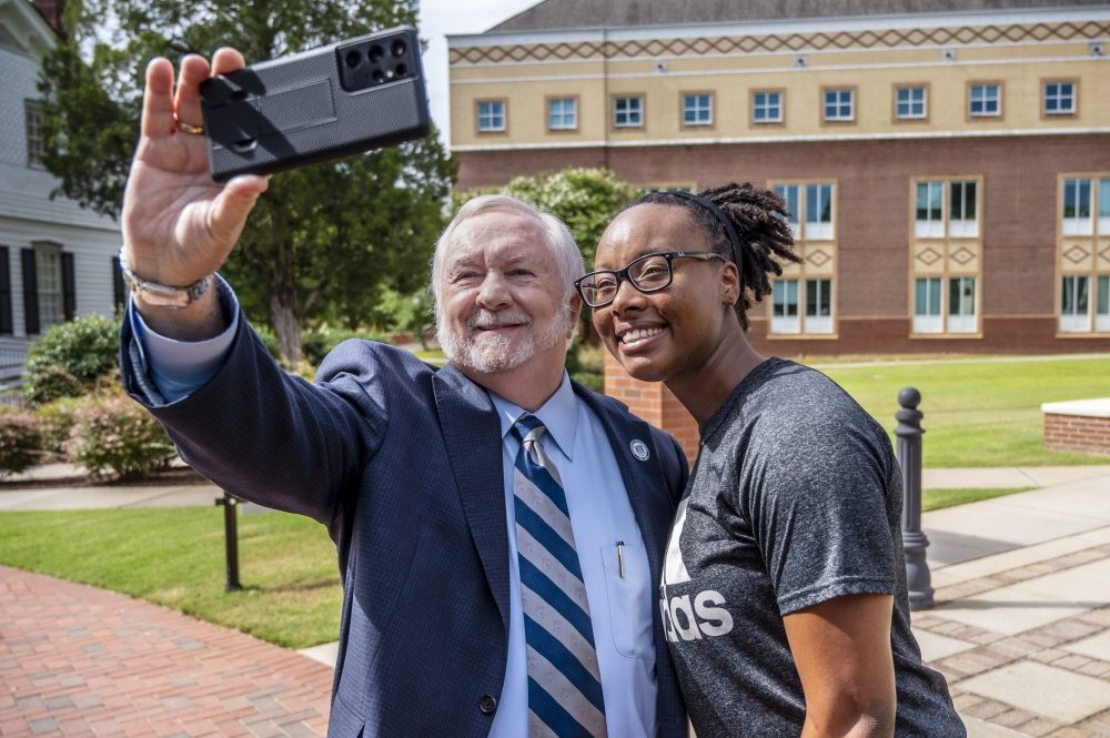 Augusta University President Brooks A. Keel, PhD takes a selfie with MCG student Donnyell Roberson on the Summerville Campus Wednesday morning. Taking a selfie with the president has become an Augusta University tradition. Any time you see President Keel on campus, he is always willing to take a selfie with students, faculty and staff. You can check out his latest selfie activity on Twitter @PresKeel.  7/7/21 10:06:49 AM  Photo by Michael Holahan/Augusta University  Job #