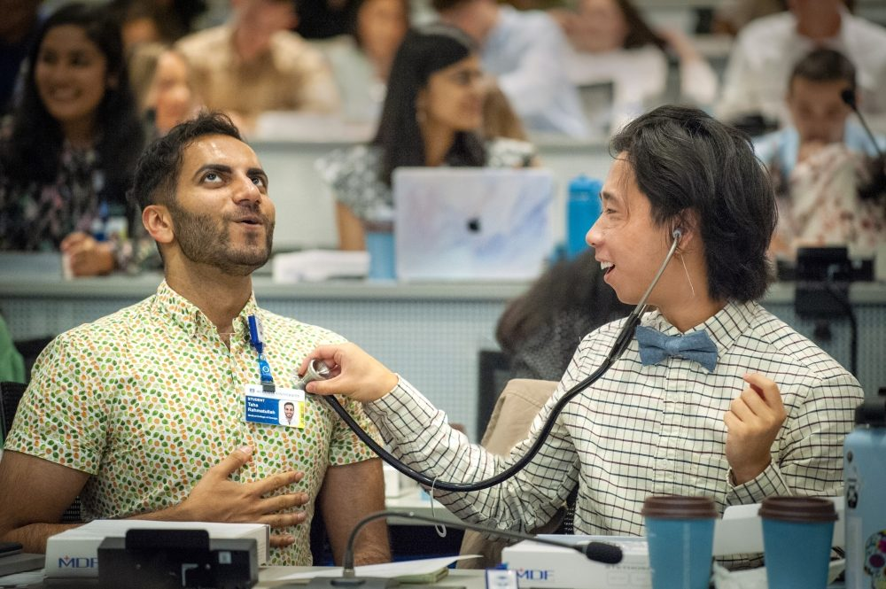 Incoming first year Medical College of Georgia student, Taha Rahmatullah, left, takes a deep breath as classmate Eddie Xie listens with his new stethoscope at the J. Harold Harrison, M.D. Education Commons on the Augusta University Health Sciences campus Monday morning July 26, 2021. Incoming medical students were given new stethoscopes courtesy of MCG alumni who included hand written notes to encourage the new students.   7/26/21 12:24:41 PM  Photo by Michael Holahan/Augusta University  Job #414021