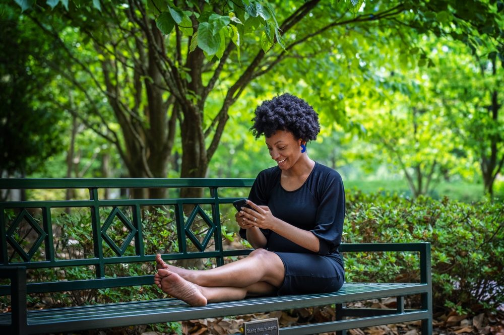 Augusta University staffer and student Monet Robinson takes a break on a shady bench to check her cell phone at the AU Summerville campus in Augusta, Ga., Friday afternoon June 4, 2021.  Photo by Michael Holahan/Augusta University  Job #